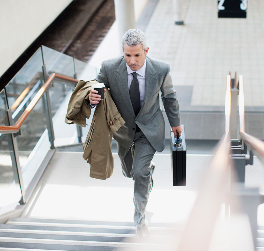 A businessman climbs the stairs up from a train platform