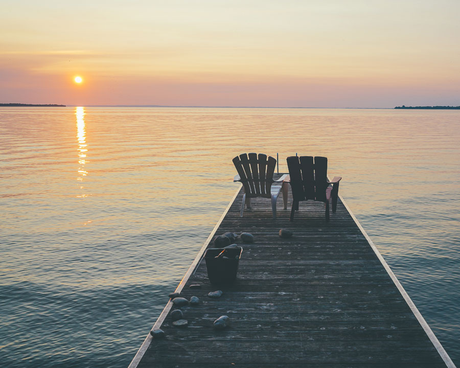 Two muskoka chairs sitting on the edge of a dock at sunset.