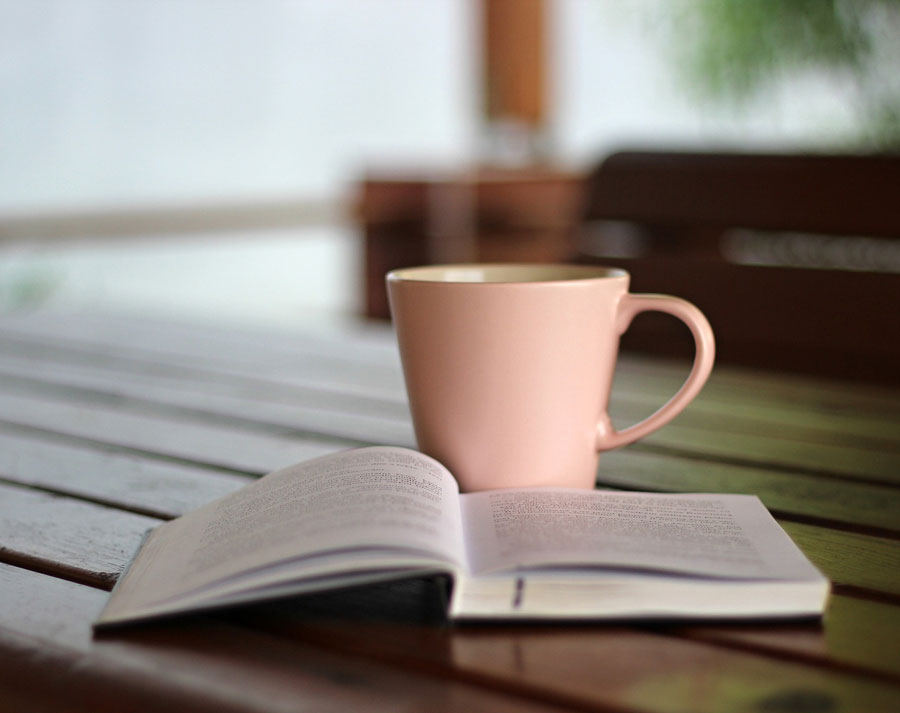 An open book on a table next to a cup of coffee