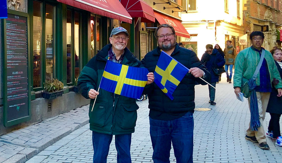Tim Johnson and his father each hold a Swedish flag during a visit to the country.
