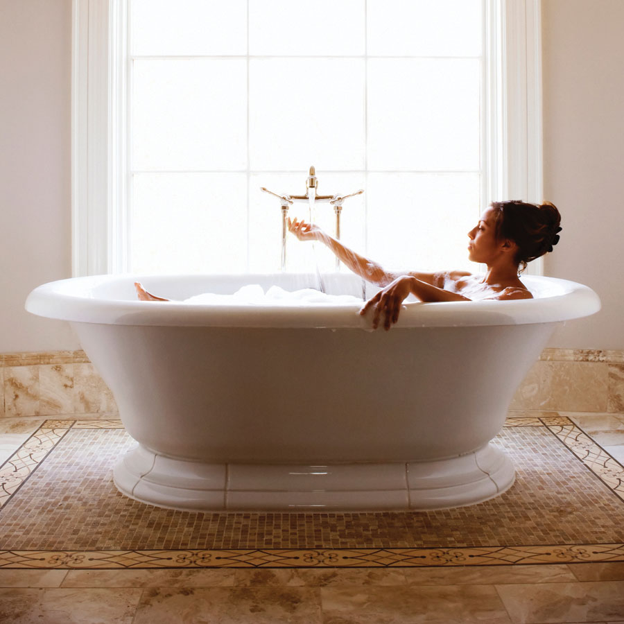 A woman in a bathtub in front of a large sunlit window.