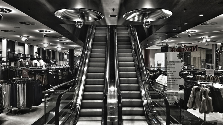 Black and white photo of escalator at department store.