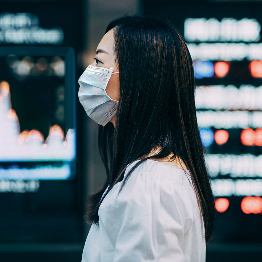 Economic and financial impact during the Covid-19 health crisis deepens. Businesswoman with protective face mask standing in front of stock exchange market display screen board on the street showing stock market crash sell-off in red colour