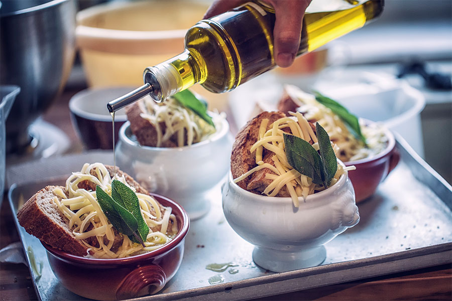 Preparing french onion soup with delicious slowly cooked onions, toasted bread, cheese and fresh sage