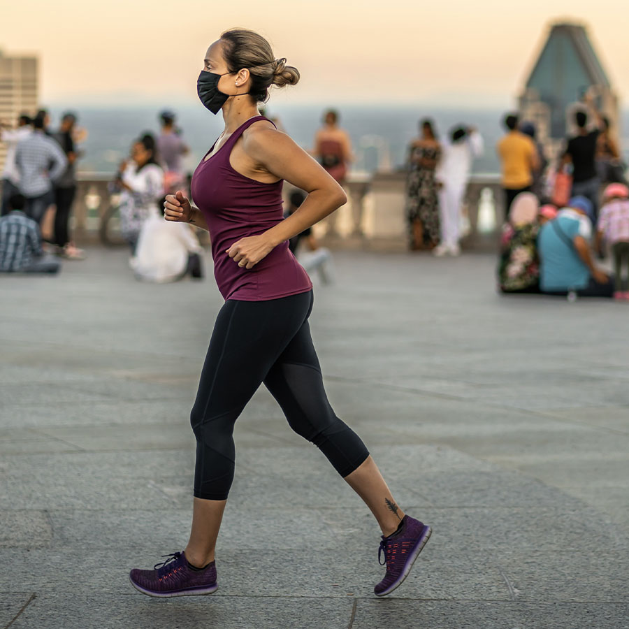 Portuguese woman running with a face mask on Kondiaronk beveldere with people looking at the Montreal downtown skyline in background during sunset in summer.