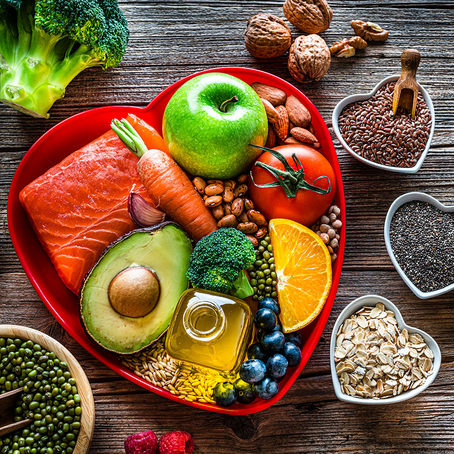 Healthy eating: group of fresh multicolored foods to help lower cholesterol levels and for heart care shot on wooden table. The composition includes oily fish like salmon. Beans like Pinto beans and brown lentils. Vegetables like garlic, avocado, broccoli, eggplant and tomatoes. Fruits like apple, grape, orange and berries. Nuts like almonds and walnuts. Soy products like tofu and soybeans. Cereals and seeds like chia seeds, flax seeds, oatmeal and barley. Olive oil, dark chocolate and yogurt with added sterols and stanols. (Photo, fcafotodigital/Getty Images)