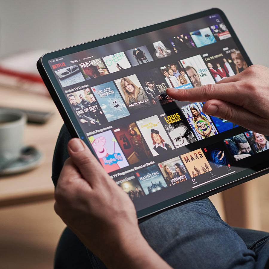 Detail of a mans hand scrolling through Netflix on an Apple iPad Pro