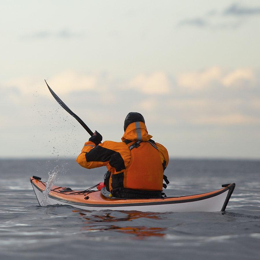 mature man steering his sea kayak through calm waters around Reykjavik