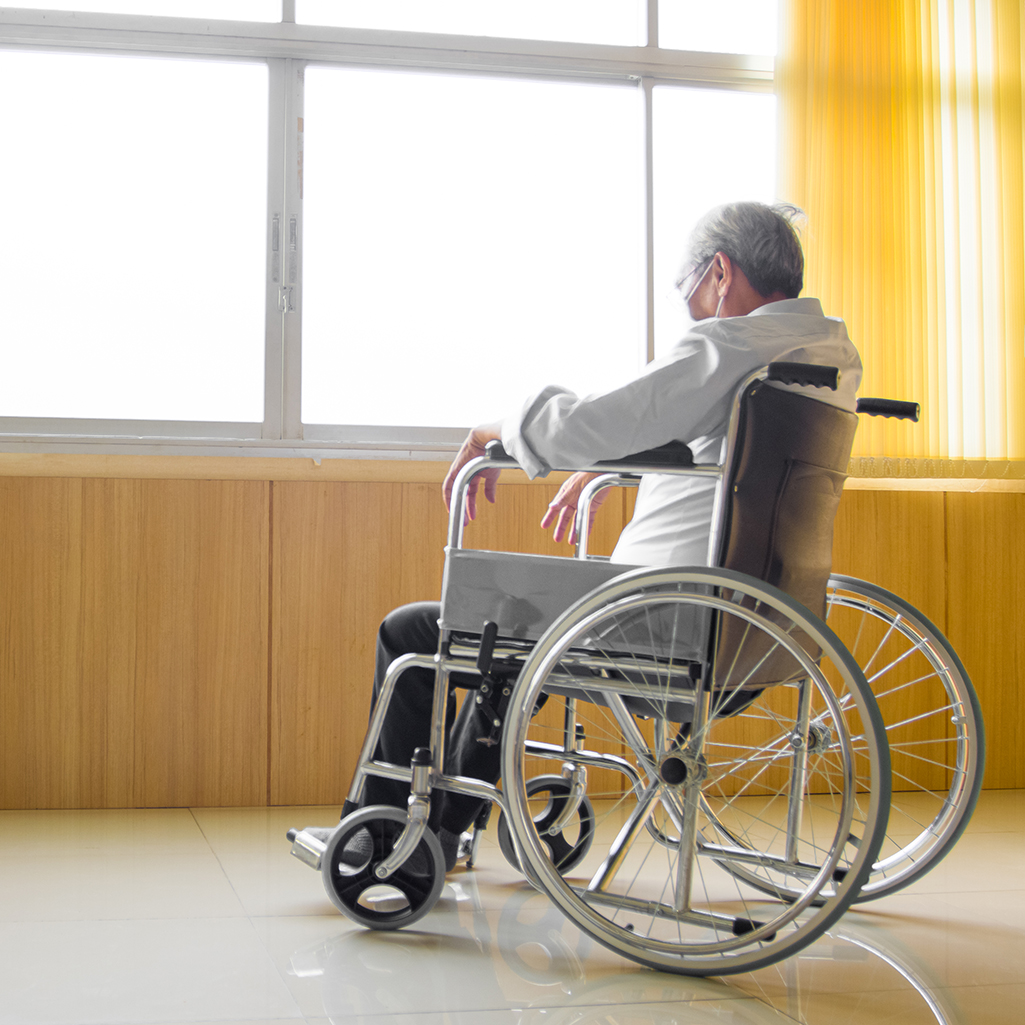 Elderly Asian person is sitting on a wheelchair, alone by a window.