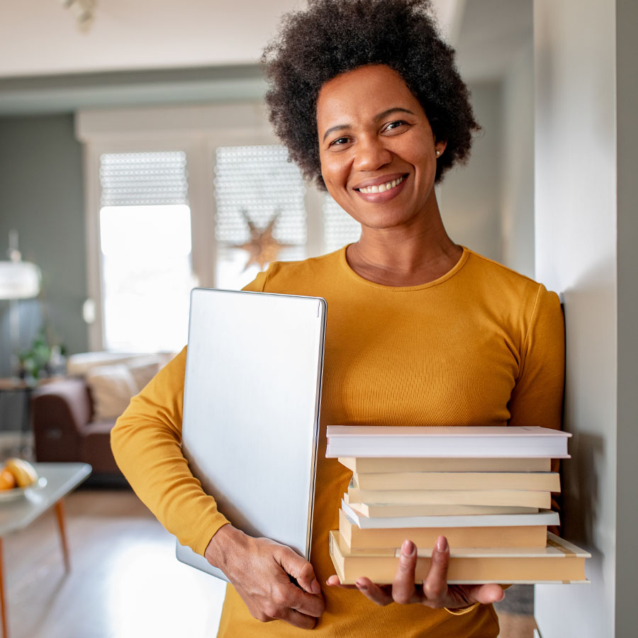 Portrait of woman holding a stack of books and a laptop, smiling to camera, from her living room.