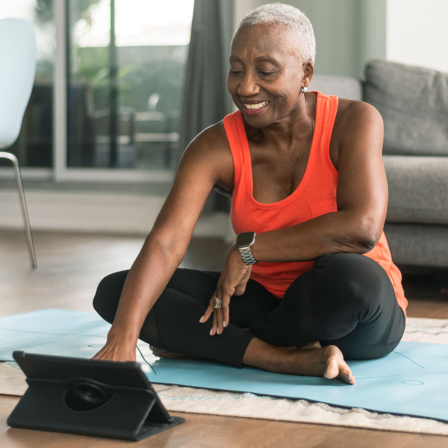 A beautiful senior woman takes an online yoga class. She is interacting with the teacher on her tablet and about to commence her class. She is wearing casual active wear and is taking the class in her lounge room. She is sitting on a blue yoga mat.