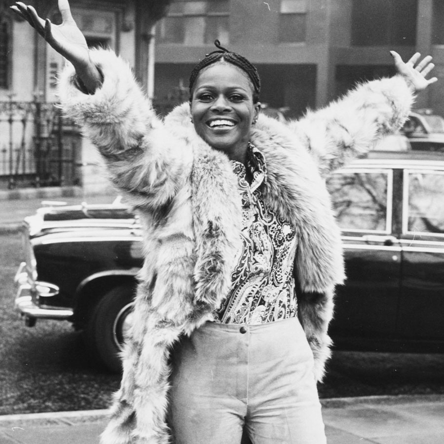 Portrait of Academy Award winning American actress Cicely Tyson smiling and raising her arms in the air during a visit to London.