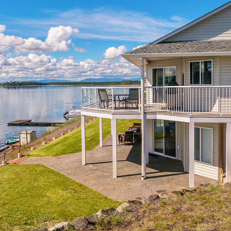 A large two-story house with beige vinyl siding, a shingled roof, a large outdoor deck and patio, with outdoor furniture situated on a freshwater lake. There is a a dock with a sitting area and equipment for water sports.