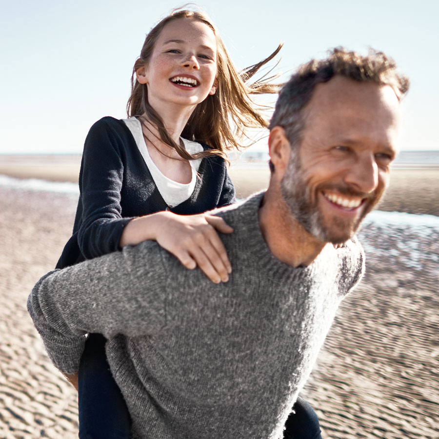 Happy father piggybacking his daughter on the beach.