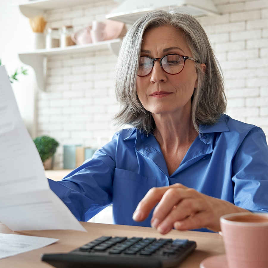 Senior mature business woman holding paper bill using calculator.