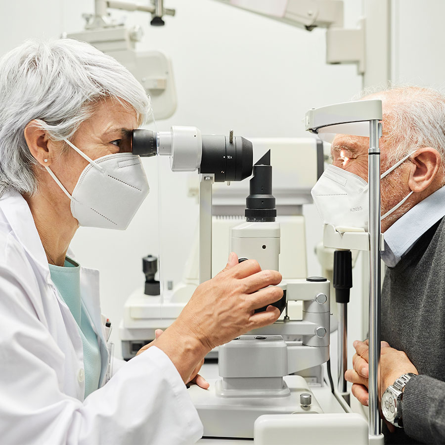 Ophthalmologist examining senior man's eye while wearing protective face mask.