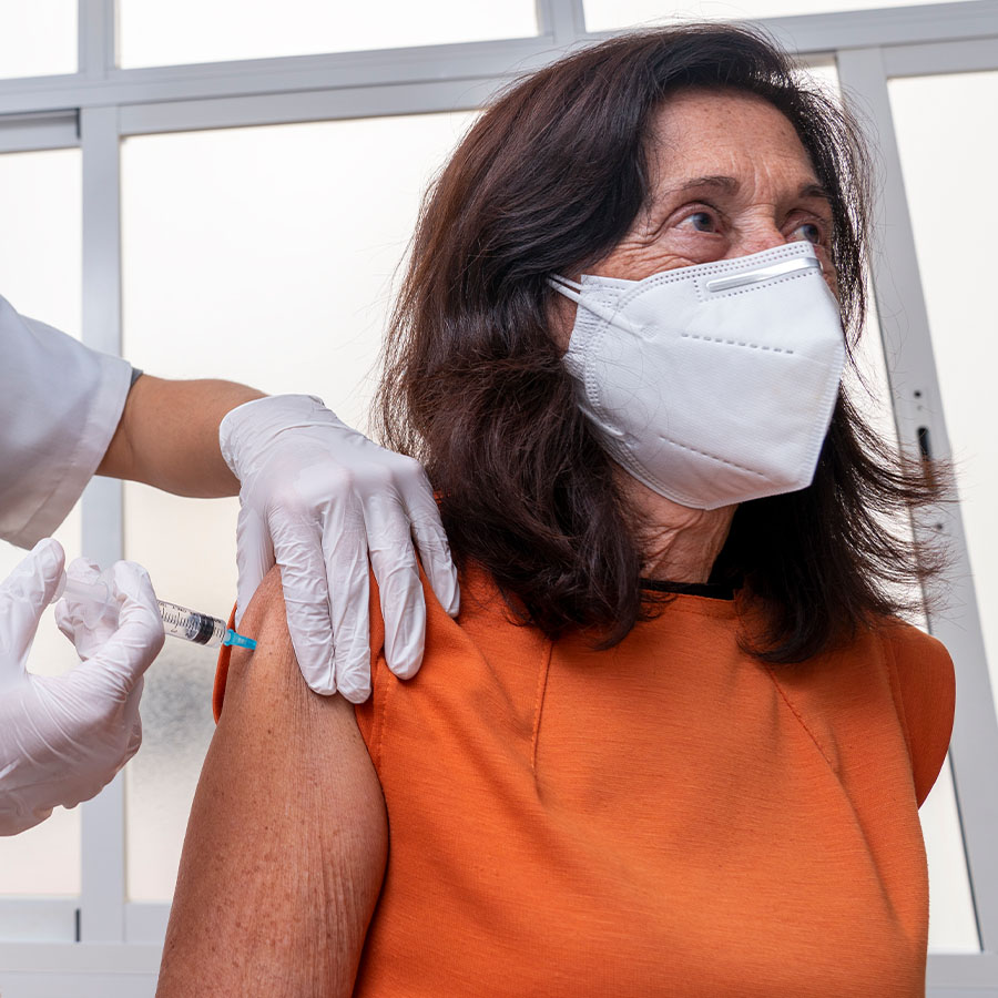 Latin senior woman getting a COVID-19 vaccine by a doctor.