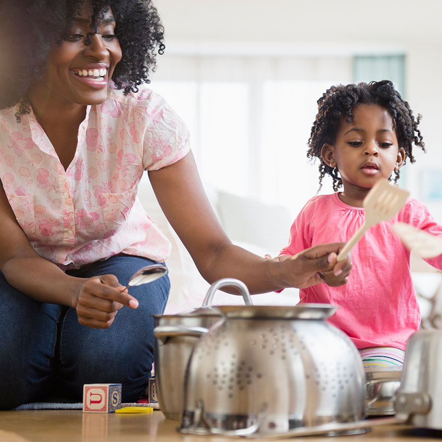 Mother and daughter playing music with pots and pans.