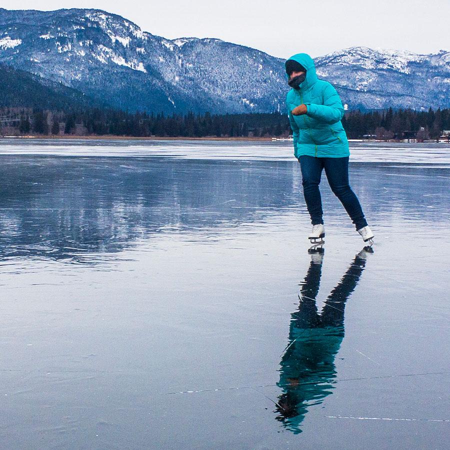 Single woman having fun ice skating on frozen Alta Lake, Whistler, British Columbia, Canada.