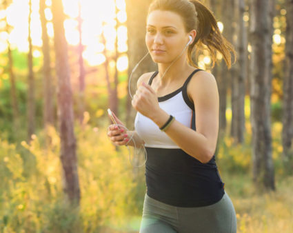 Young woman jogging with a cell phone strapped to her arm.