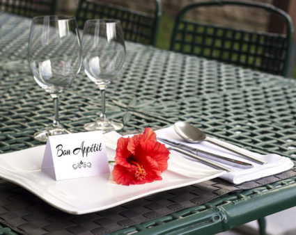 "A table place setting with a note on the plate that reads ""bon apatit"" beside a flower."