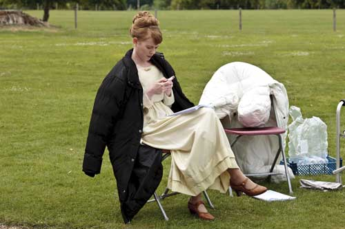 DAS2 BTS: Zoe Boyle (Lavinia Swire) checks her phone while relaxing between takes