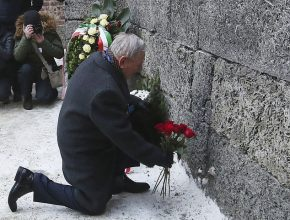 A holocaust survivor places flowers in commemoration of the people killed by the Nazis at the former Auschwitz Germany Nazi death camp in Oswiecim, Poland, Friday, Jan. 27, 2017, on the International Holocaust Remembrance Day that marks the liberation of the Auschwitz Nazi death camp on Jan. 27, 1945.(AP Photo/Czarek Sokolowski)