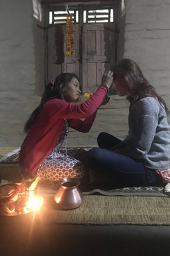 A Volunteer receives a blessing from a Nepali host sister, both are sitting on a floor in a dark room
