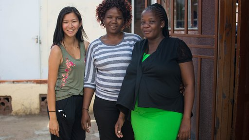 An Asian-American female stands outside in the sun with her friends in Botswana