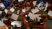 Overhead shot of students in South Africa. The students are wearing burgundy sweaters for their uniforms. There are books and