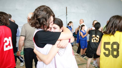 Two basketball players embrace after an emotional win.