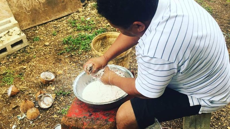 A man sits on a stool making coconut milk in a large metal bowl on the ground. His back is to the camera.