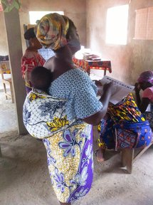 "A Beninese ""mama"" practicing accounting with her baby."