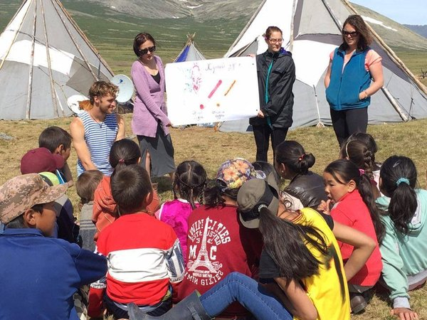 A group of girls sits outside in front of camping tents listening to leadership lesson from a Volunteer and community leader.