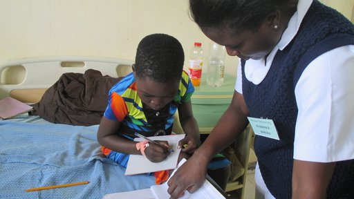 Florence, a nursing student, with Agnes, explaining the lesson book in Chichewa