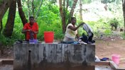 Two Malawian women wash clothes at a borehole
