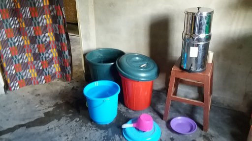 Colorful buckets sit on the floor next to a water filter.