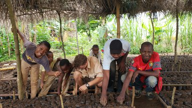Logan and his community members plant the cocoa seeds in the nursery