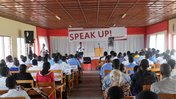 Image taken from the rear of the room with participants seated and Speak Up banner in front of the room