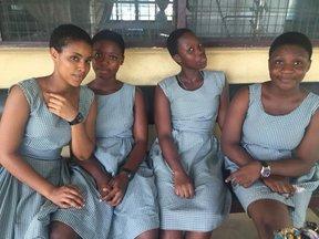 Four Ghanaian women sit on a bench