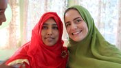 Two women pose for a photo wearing hijab. One is in a red hijab, the other in green.