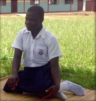 Akello sitting on a straw mat in her school uniform.