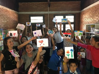 Members of the Art Club at the Escuela Basica show off their finished drawings/paintings.