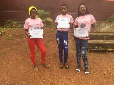 A group of students standing outside holding up their certificates.