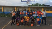 A basketball team of young Jamaican men and women pose with donate basketballs with volunteer Don Holly.