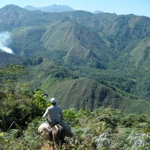 A man sits on a donkey, facing a lush, mountainous landscape. There is a small plume of smoke to the left of the frame.