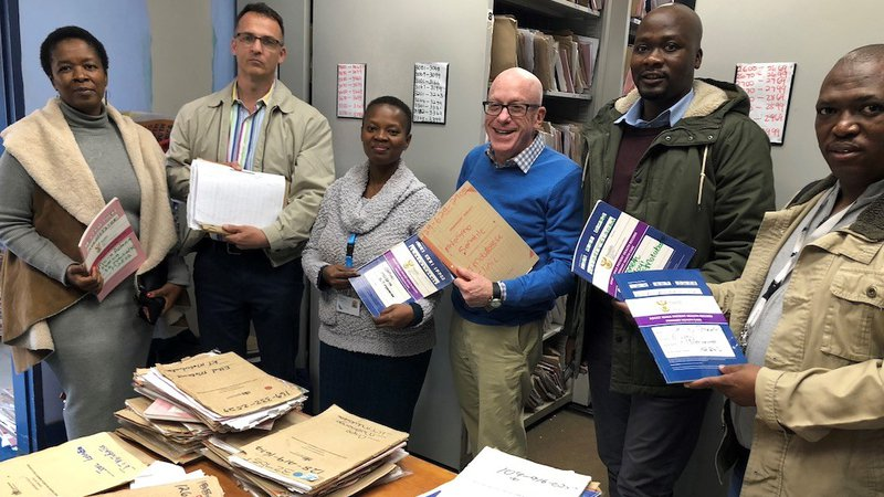 White male volunteer stands in health clinic with South African colleagues with files and all are smiling.