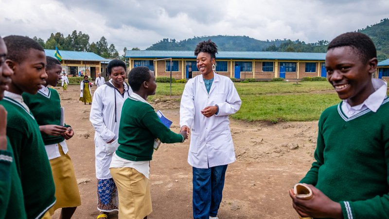 PCV Brina greets students in the school yard and shares a laugh and a smile