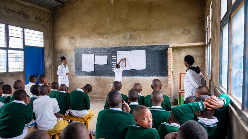 PCV Brina coteaching with a student at the chalk board