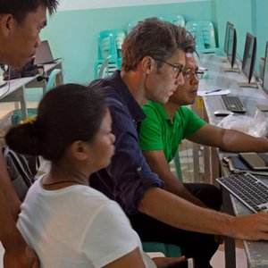 A male Caucasian Peace Corps Volunteer sits in front of a computer, looking intently at a land use map model. 3 of his Filipi